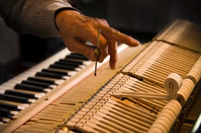 Person tuning a piano